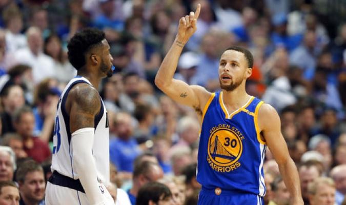De los Warriors de Golden State Stephen Curry, celebrando una canasta de 3 puntos en la segunda mitad de un partido de la NBA, frente a Wesley Matthews de los Mavericks de Dallas.