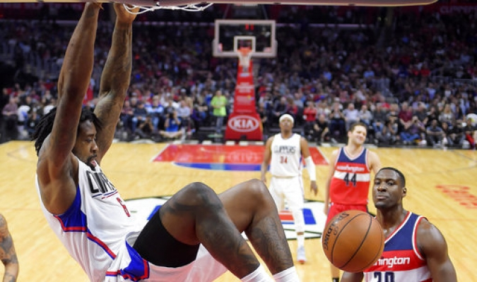 DeAndre Jordan de Los Angeles Clippers, a la izquierda, observa como el frances Ian Mahinmi de los Washington Wizards , intenta defender durante la segunda mitad de un partido de baloncesto de la NBA / Fotos: AP