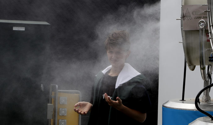 Un espectador se refresca delante de un ventilador con agua durante un partido / Foto: AP