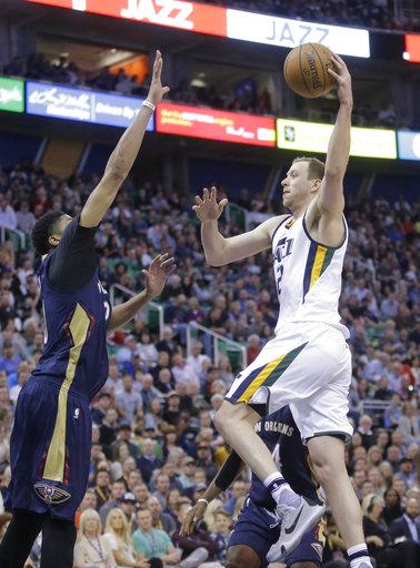 El delantero del Jazz de Utah Joe Ingles, va a la canasta cuando el delantero de los Pelicans de New Orleans Anthony Davis, a la izquierda, defiende durante la segunda mitad en un partido de baloncesto de la NBA Salt Lake City