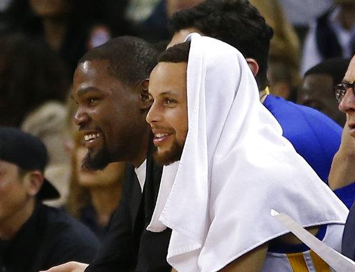 Stephen Curry de los Golden State Warriorsy Kevin Durant, desde el banquillo durante la segunda mitad contra los Minnesota Timberwolves