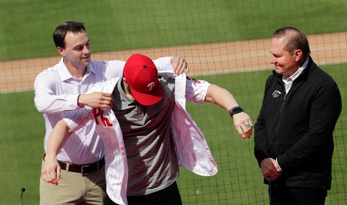 Matthew Klentak, gerente del equipo, colocando la franela a Harper/ Foto AP
