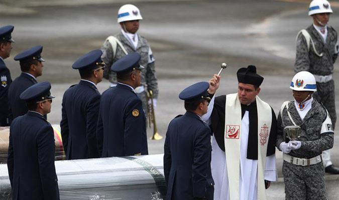 Un sacerdote católico bendice los ferétros donde se encuentran las victimas./ EFE