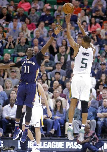 Por parte de Utah, Rodney Hood dispara al Guardia de Pelícanos de Nueva Orleans Jrue Holiday mientras este defiende durante la primera mitad en un partido de baloncesto de la NBA el lunes 27 de marzo, resultando ganadora Utah por marcador de 100-108