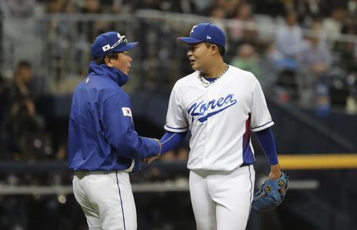 Sim Chang-min es felicitado por el coach de lanzadores /Foto AP