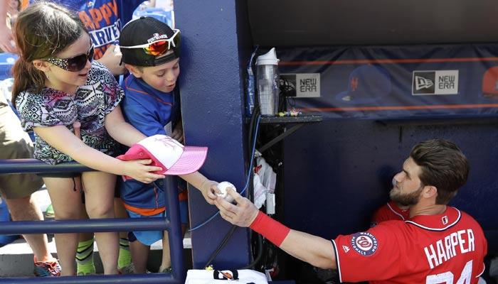 Bryce Harper le regala una pelota a un joven aficionado /Foto AP