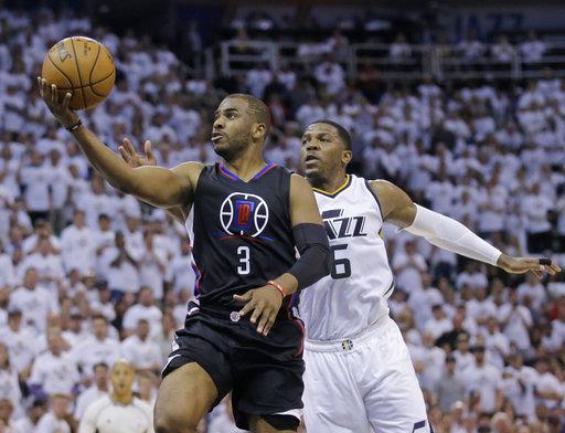 Chris Paul, guardia De Los Ángeles Clippers pone la pelota hacia arriba cuando el delantero de Utah Joe Johnson intenta defender durante la primera mitad en el Juego 4 de la serie de playoffs